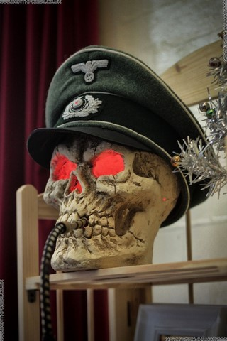 A skull with glowing red eyes and a World War Two German hat